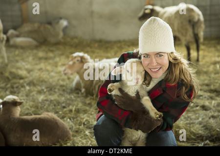 Ein Bio-Bauernhof im Winter im kalten Frühling New York Staat A Familie arbeiten, Fürsorge für die Tiere A Frau - Stockfoto