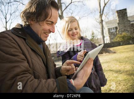 Ein Bio-Bauernhof im Winter im kalten Frühling New York State ein Mann mit einem digitalen Tablet in den Händen - Stockfoto