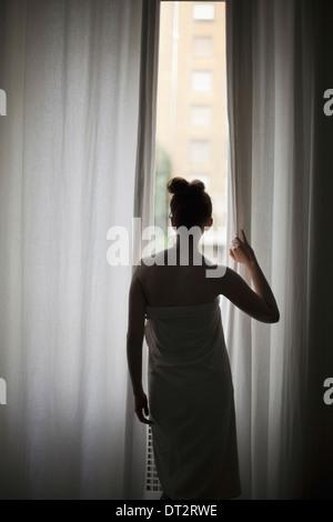 Eine junge Frau mit ihrem Haar trägt ein Badetuch Blick durch lange Vorhänge am Fenster - Stockfoto
