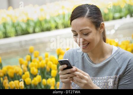 Urban Lifestyle A Frau im Park durch ein Bett von gelben Tulpen mit ihrem Mobiltelefon - Stockfoto
