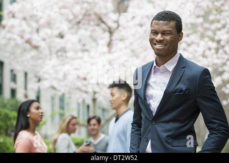 Junge Menschen im Freien in einer Stadt Park A Mann in einem Anzug, lächelnde vier Menschen in den Hintergrund mit - Stockfoto