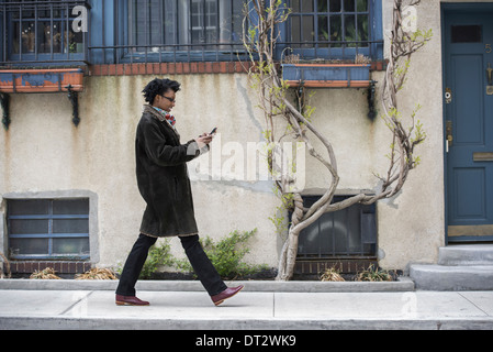 Eine Frau in einen warmen Mantel zu Fuß entlang der Straße überprüft ihr Telefon - Stockfoto