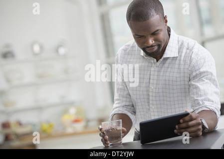 Junge Berufstätige Arbeit A Geschäftsmann in einem offenem Kragen sitzen mit einem Glas Wasser mit einem digitalen - Stockfoto