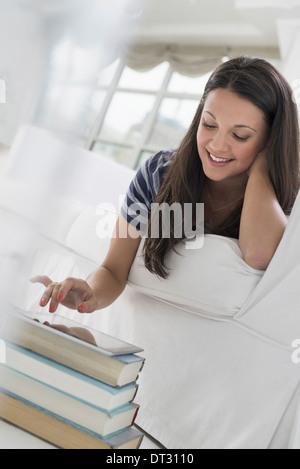 Frau liegend auf den Bauch auf dem Sofa in einer ruhigen luftig Büroumgebung mit einem Smartphone - Stockfoto