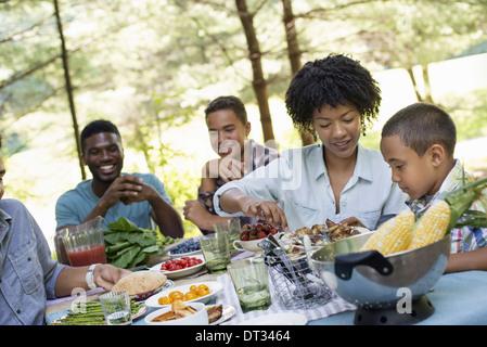 Ein Familien-Picknick in einem schattigen Waldgebiet Erwachsene und Kinder an einem Tisch reichte um Platten und - Stockfoto