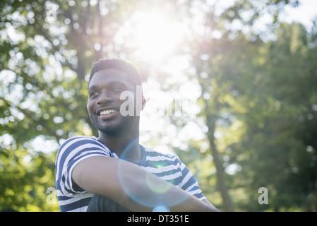 Ein Mann in einem gestreiften Hemd unter dem Schatten der Bäume - Stockfoto