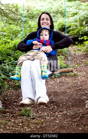 Ein kleiner Junge sitzt auf seinem Schoß Mütter, wie sie auf einer provisorischen Schaukel an einen Baum gebunden - Stockfoto