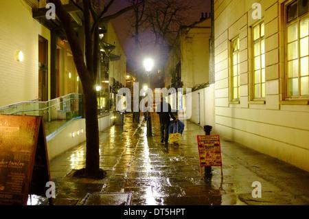 Mann mit Gepäck zu Fuß durch eine schmale Gasse in einer regnerischen Nacht in London - Stockfoto