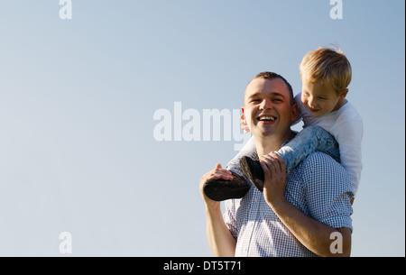Junger Vater gibt seinem Sohn eine Huckepack-Fahrt - Stockfoto