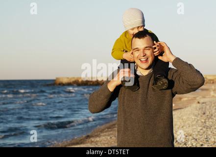 Lachend Vater geben seine Sonny eine Huckepack - Stockfoto
