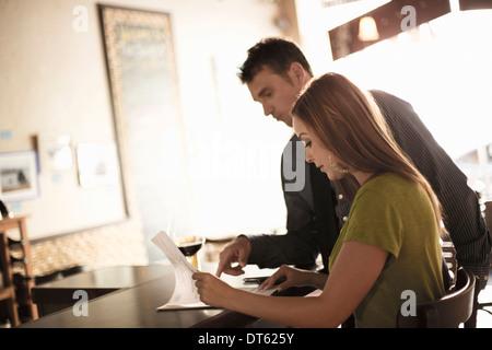 Geschäftspartner, die Papiere in eine Wein-Bar zu betrachten - Stockfoto