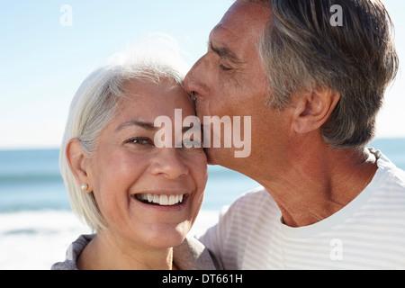 Mann küssen Frau auf Stirn