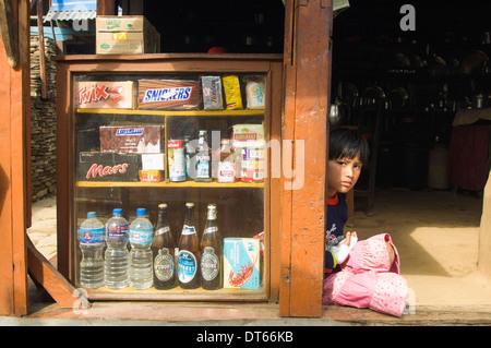 Nepal, Südasien, Pokhara. Mädchen sitzen in einem Shop Eingang auf einem trekking-Route mit westlichen Snacks zum - Stockfoto