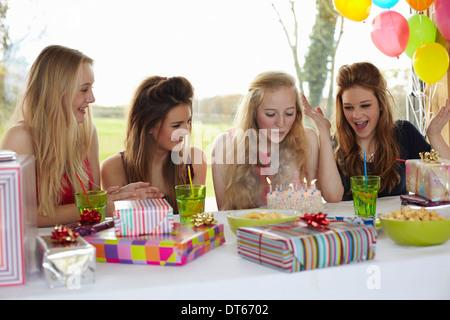 Junges Mädchen bläst Geburtstagskerzen mit Freunden - Stockfoto