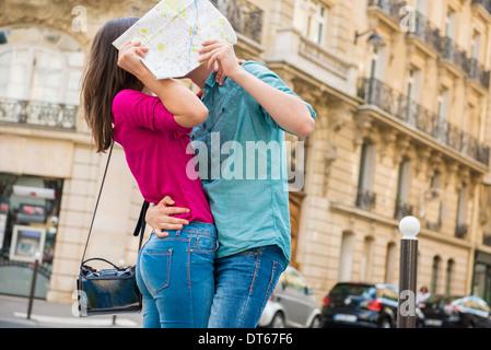 Junges Paar versteckt sich hinter Karte, Paris, Frankreich - Stockfoto