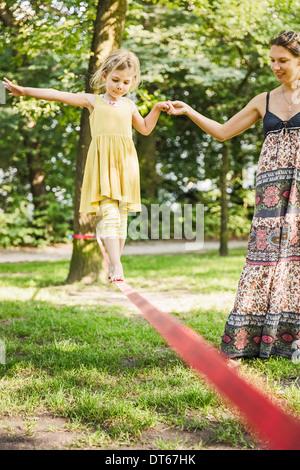 Junges Mädchen mit Mutter gehen Slackline im park - Stockfoto