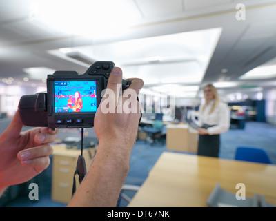 Büroangestellte thermische Infrarot-Aufnahmen im Büro um Wärme Effizienz überprüfen - Stockfoto