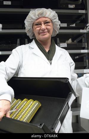 Wissenschaftlerin mit Tablett im Laserlabor - Stockfoto