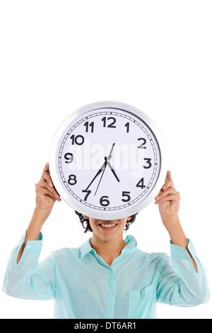 hispanische Geschäftsfrau Blick in die Kamera und versteckt sich hinter der großen Uhr auf weißem Hintergrund - Stockfoto