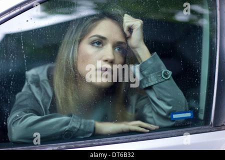 Unglückliche junge Frau wartet im Auto