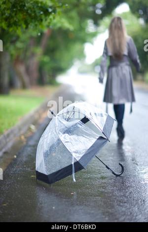 Junge Frau und gebrochenen Regenschirm im park - Stockfoto