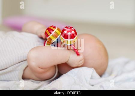 Babymädchen liegend mit Rassel für Gesicht - Stockfoto