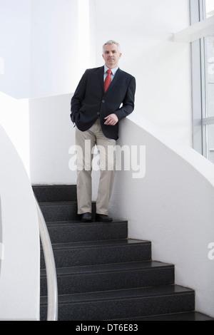 Porträt von reifer Geschäftsmann auf Büro-Treppe - Stockfoto