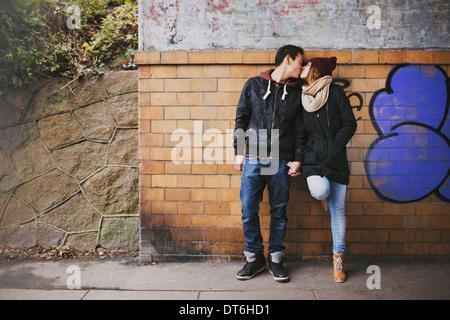 Liebevolle Teenager-Paar küssen im freien gegen eine Wand auf Straße. Mischlinge-paar in der Liebe. - Stockfoto