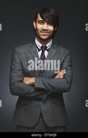 Porträt von glücklich junger Geschäftsmann lächelnd mit seine Arme verschränkt. Gut aussehend männlichen executive - Stockfoto