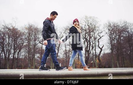 Niedrigen Winkel Blick auf hübscher junger Mann mit seiner Freundin zu Fuß zusammen halten die Hände im Park. Gemischte - Stockfoto