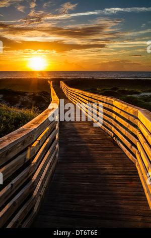 Einen sonnigen Promenade führt zum Sonnenaufgang über den Strand. Amelia Island, Florida. - Stockfoto