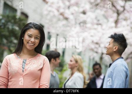 Leben in der Stadt im Frühjahr. Junge Menschen im Freien in einem Stadtpark. Eine Frau in einem rosa Hemd mit vier - Stockfoto