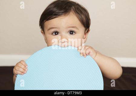 Ein 8 Monate altes Baby junge tragen Stoffwindeln, hält eine große blaue Scheibe und den Rand zu kauen. - Stockfoto