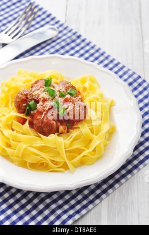 Fleischbällchen mit Pasta und Parmesan in weißer Teller auf hölzernen Hintergrund - Stockfoto