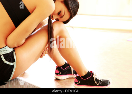 Portrait eines jungen müde passen Frau sitzt auf dem Boden in Turnhalle - Stockfoto