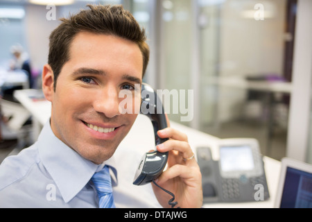 Geschäftsmann am Telefon im Büro, auf der Suche Kamera Lächeln - Stockfoto