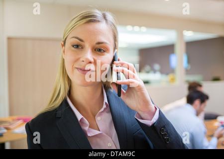 Geschäftsfrau in ihrem Büro telefonieren - Stockfoto