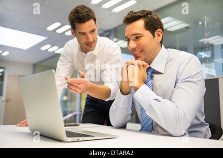 Zwei hübsche Geschäftsleute arbeiten gemeinsam an einem Laptop im Büro - Stockfoto