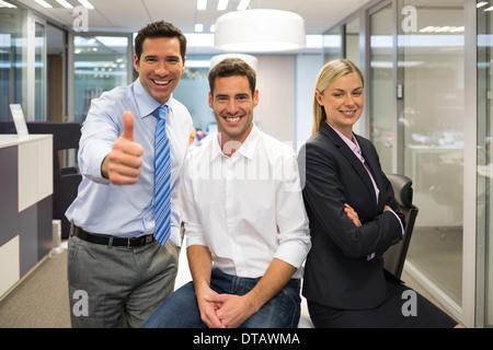 Porträt des freudigen Geschäftsteam, Mann Daumen auftauchend, Office-Hintergrund - Stockfoto