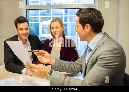 Junges Paar Vertragsunterzeichnung im Büro mit Immobilien, neue Eigentümer - Stockfoto