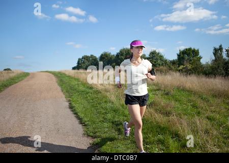 Junge weibliche Läufer läuft neben Feldweg - Stockfoto
