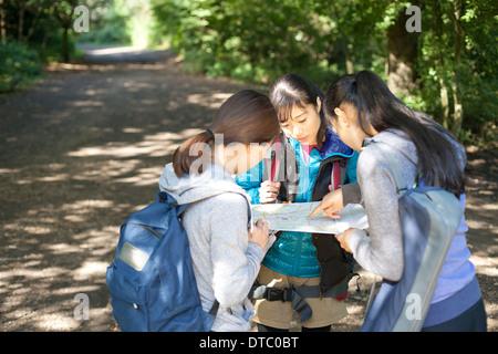 Drei junge weibliche Wanderer auf der Suche auf Karte - Stockfoto
