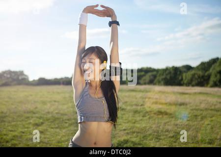 Junge weibliche Läufer Arme dehnen und Aufwärmen Stockfoto