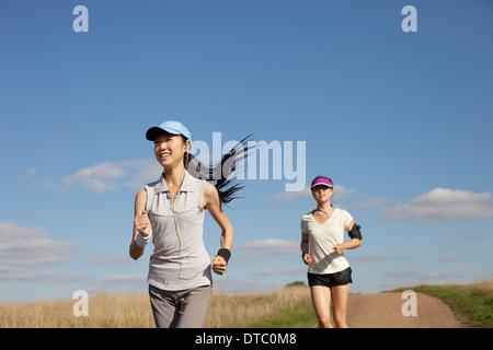 Zwei junge Frauen laufen auf Feldweg - Stockfoto