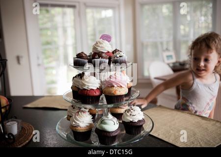 Weiblichen Kleinkind Blick auf Etagere voller Muffins - Stockfoto