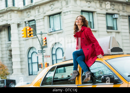 Junge weibliche Touristen sitting on Top of gelbes Taxi, New York City, USA - Stockfoto