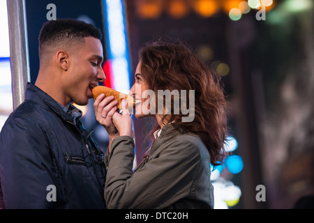 Junge Touristen paar Teilen Hotdog, New York City, USA - Stockfoto