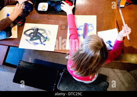 Zwei junge Geschwister malen am Tisch Stockfoto