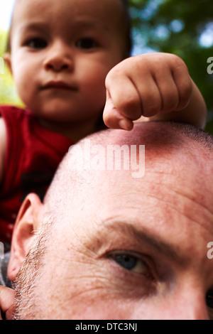 Nahaufnahme von Vater Baby Sohn auf den Schultern tragen - Stockfoto