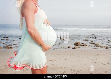 Abgeschnitten Bild der schwangeren jungen Frau am Strand - Stockfoto